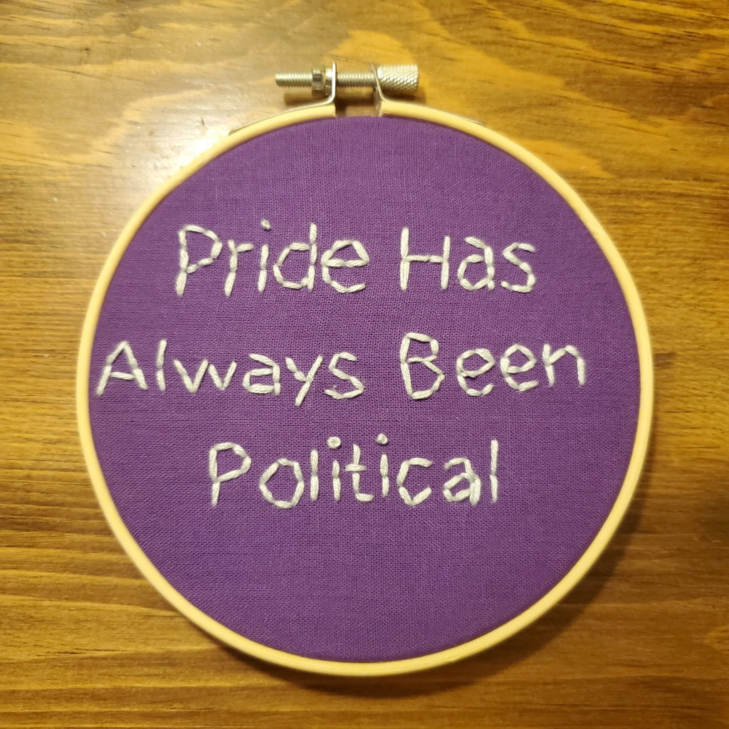 "Item: Pride Has Always Been Political Embroidery. Five inch circular embroidery reading ""Pride Has Always Been Political"" in yellow on a purple background."