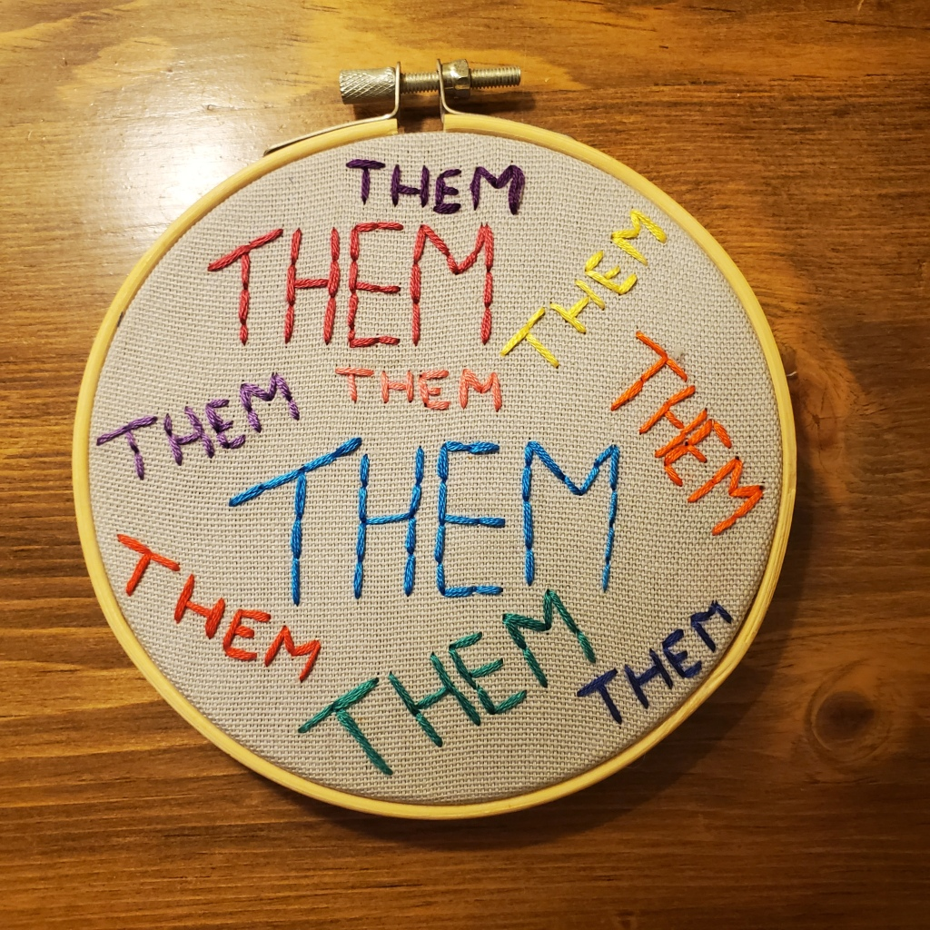 """Item: Them Pronoun Embroidery. A five-inch circular embroidery on grey fabric with """"Them"""" written in neon colours."""